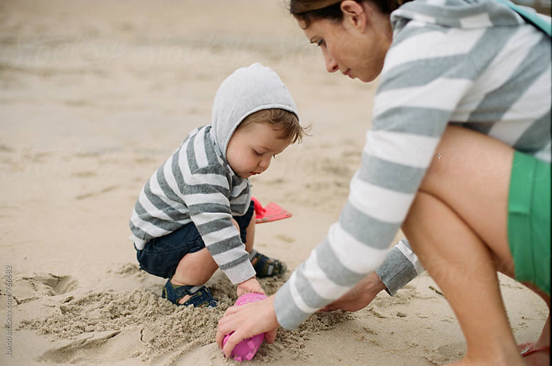 Cute young boy playing with his mother in the sand on a beach by Jakob for Stocksy United