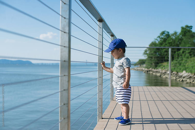 Little kid at the lake by Lauren Naefe for Stocksy United