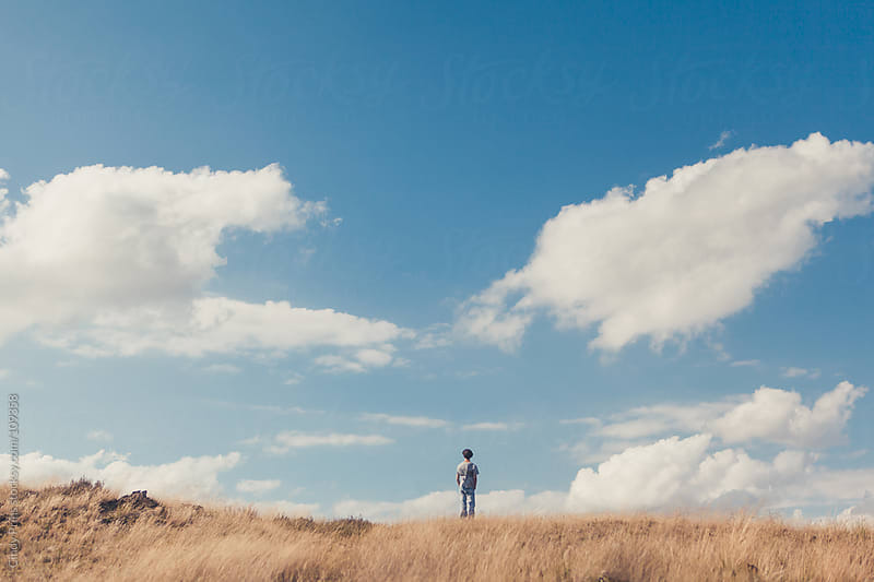A teenage boy standing on a dune with a blue sky and clouds by Cindy Prins for Stocksy United