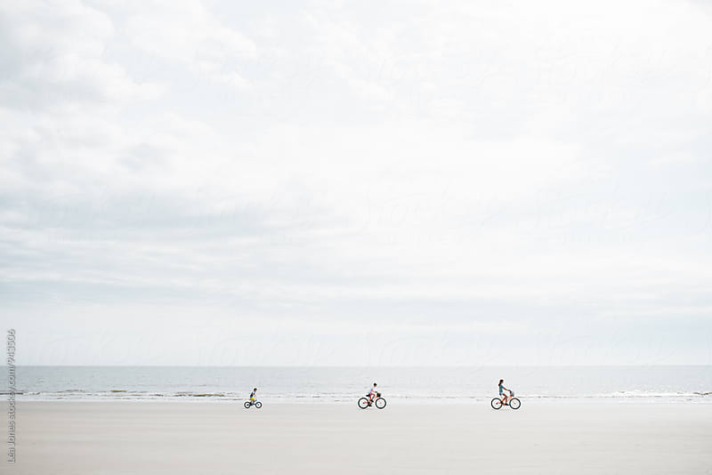 three kids riding their bikes on the beach by Léa Jones for Stocksy United