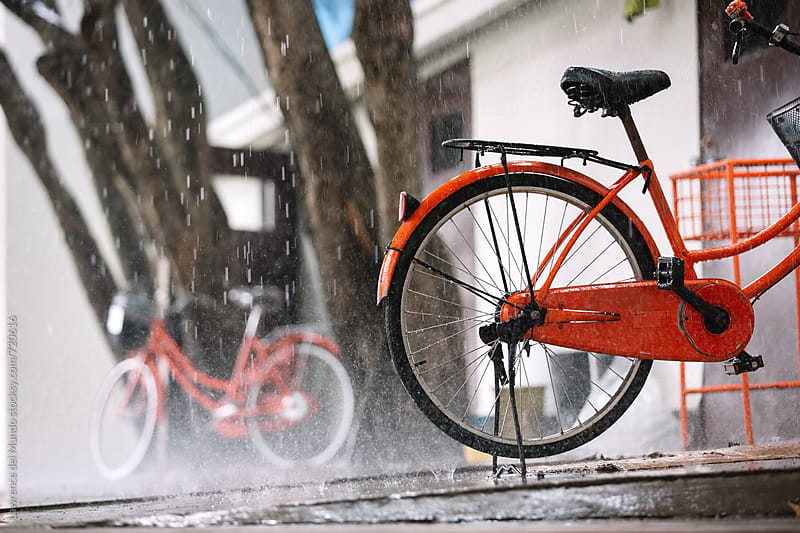 Rear wheel of a parked orange bike under the pouring rain by Lawrence del Mundo for Stocksy United