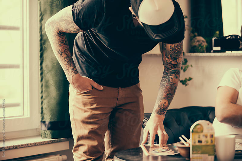 Man in Tattoo Studio reading magazine by Urs Siedentop & Co for Stocksy United