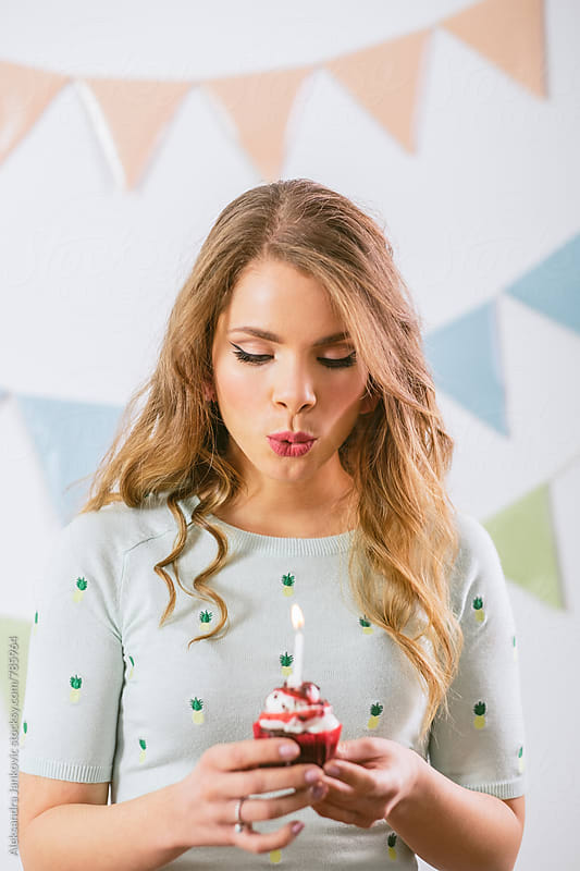 Young Woman Blowing a Candle for Birthday by Aleksandra Jankovic for Stocksy United