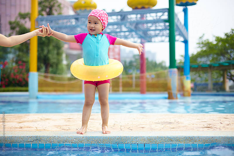 happy little asian girl in the swimming pool by Bo Bo for Stocksy United