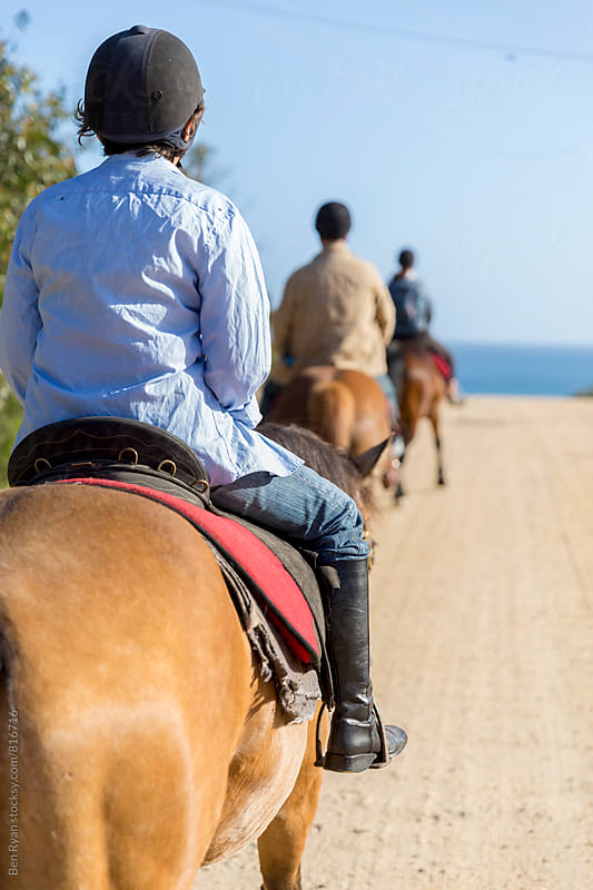 Rear view of trail riders on their horses riding towards ocean by Ben Ryan for Stocksy United