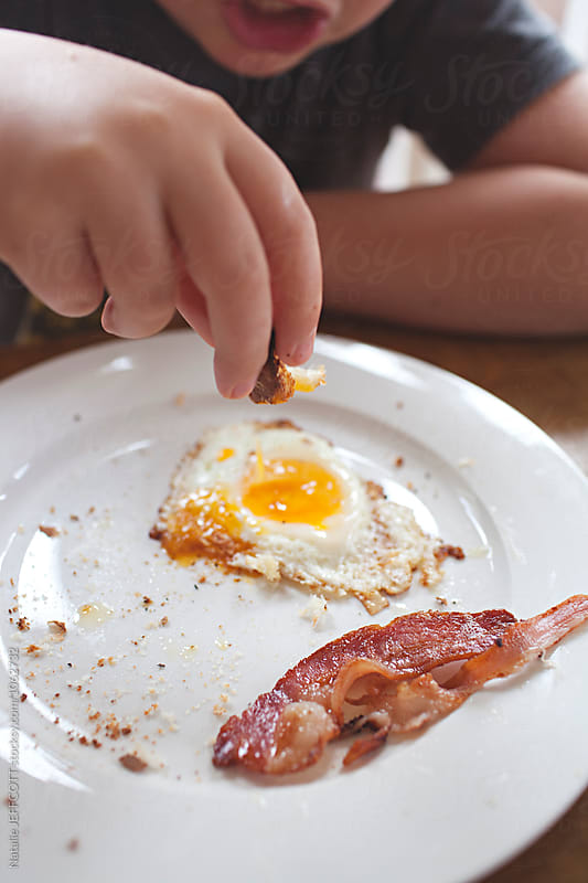 Young boy eating fried eggs and bacon at home for breakfast by Natalie JEFFCOTT for Stocksy United