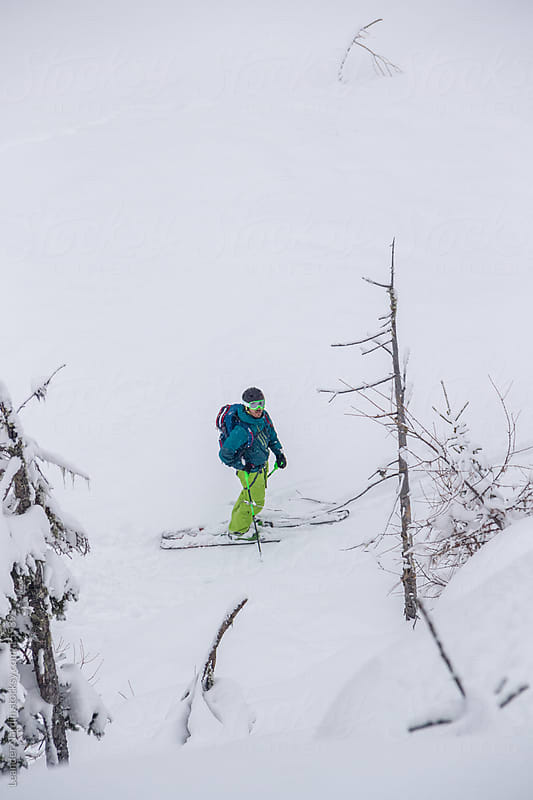 Skiier standing in a snowcovered forest by Leander Nardin for Stocksy United