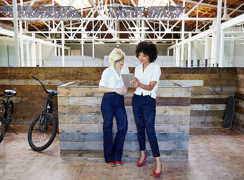 Portrait of two millennials looking at ipad at office by Trinette Reed for Stocksy United