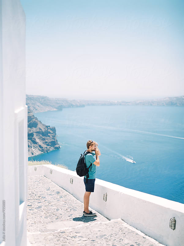 Man taking photos of a beautiful view at Santorini, Greece by Julia Kaptelova for Stocksy United
