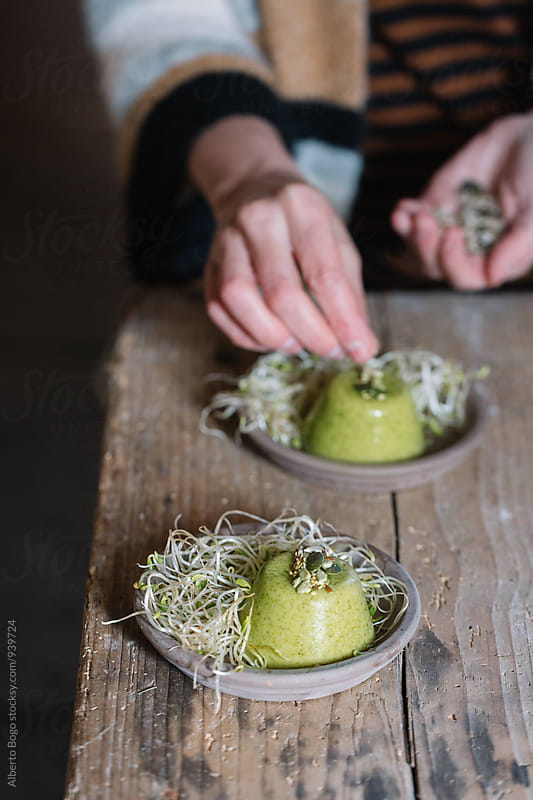 Bean sprouts with broccoli mousse and seeds in close-up by Alberto Bogo for Stocksy United