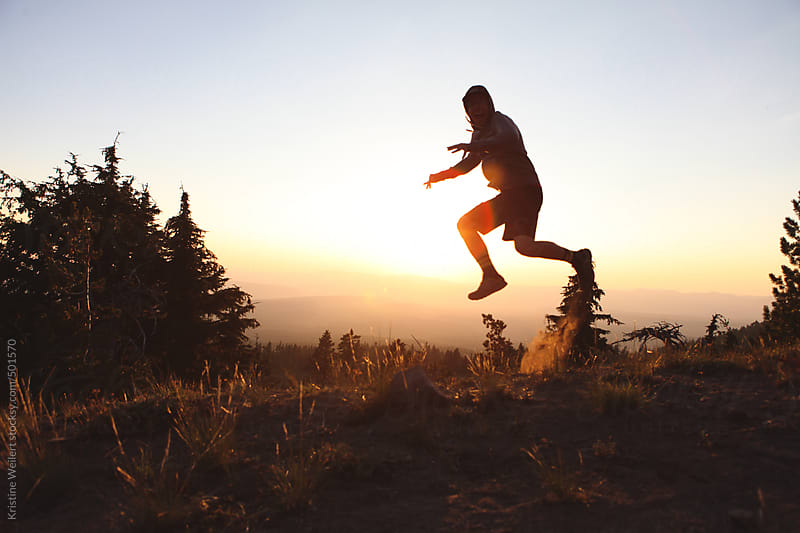 Man jumping in the air with sunset behind him by Kristine Weilert for Stocksy United