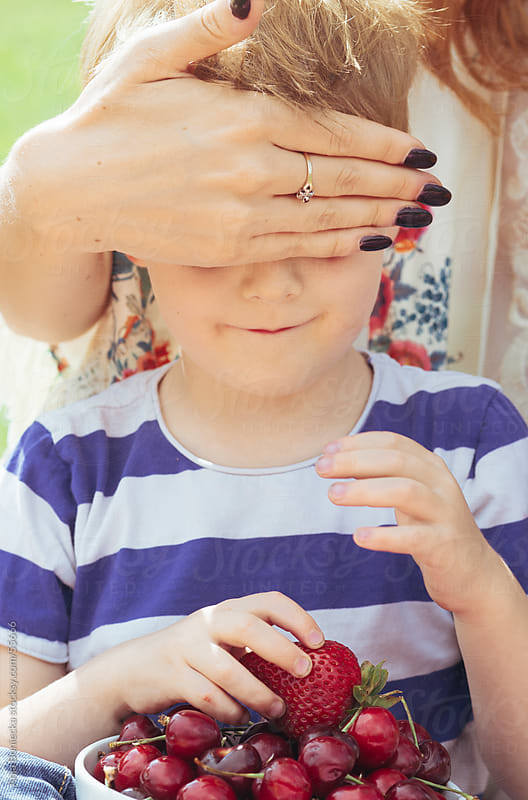 Mom cover her son's eyes, who's holding a bowl of cherries by Ania Boniecka for Stocksy United