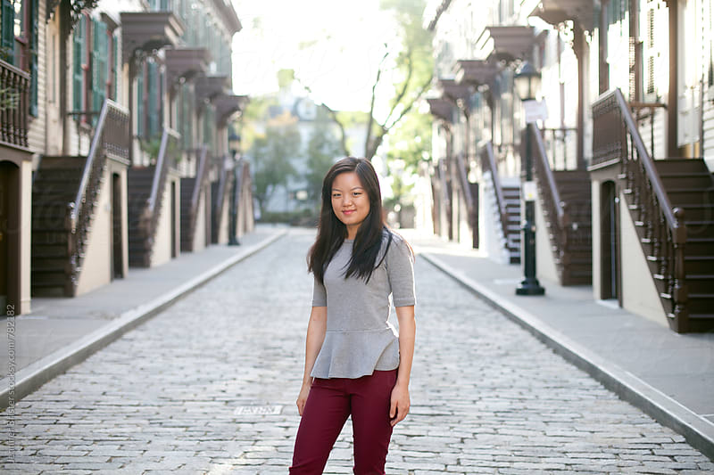 Young woman standing on street by Jen Brister for Stocksy United