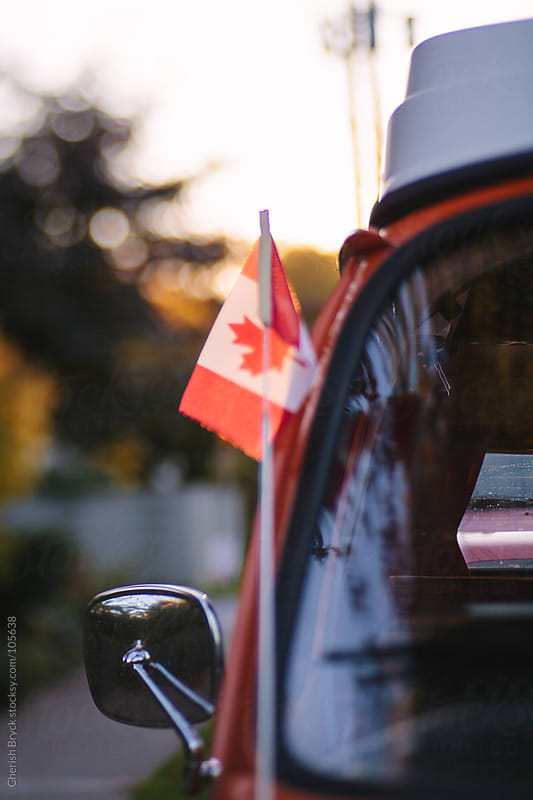 A small Canada flag is attached to a orange camper van. by Cherish Bryck for Stocksy United