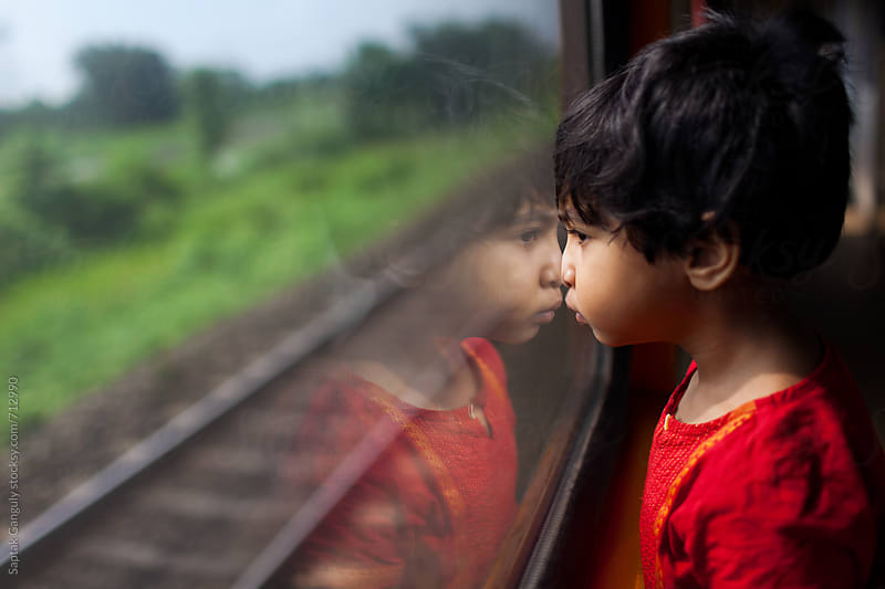 Little girl looking through the train window in a contemplative mood by Saptak Ganguly for Stocksy United