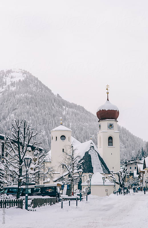 Snow covered mountain village with a church in the Austrian Alps by Soren Egeberg for Stocksy United
