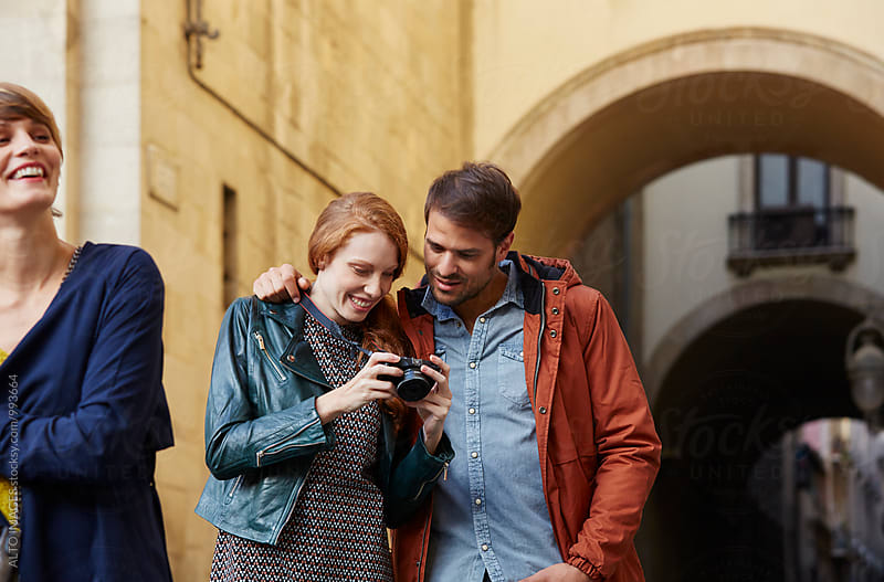 Couple Looking At Photograph On Camera In City by ALTO IMAGES for Stocksy United