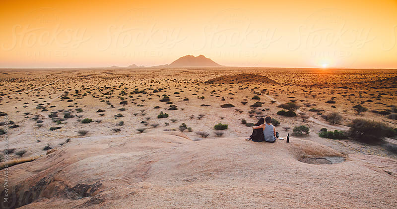 Couple on a mountain enjoying the sunset by Micky Wiswedel for Stocksy United