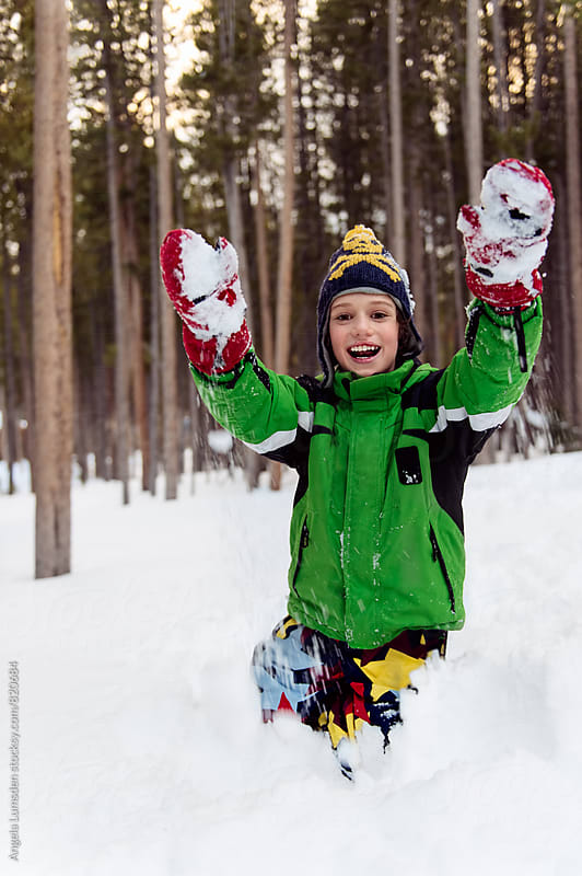 Happy boy playing in snow in snow clothes by Angela Lumsden for Stocksy United