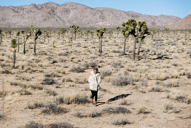Woman walking through desert with fur coat on. Joshua Tree, California by Jeremy Pawlowski for Stocksy United