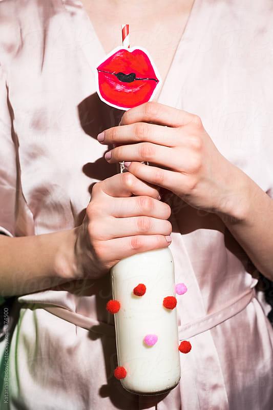 Woman Holding Funny Bottle of Milk With Red Lips on the Straw by Katarina Radovic for Stocksy United