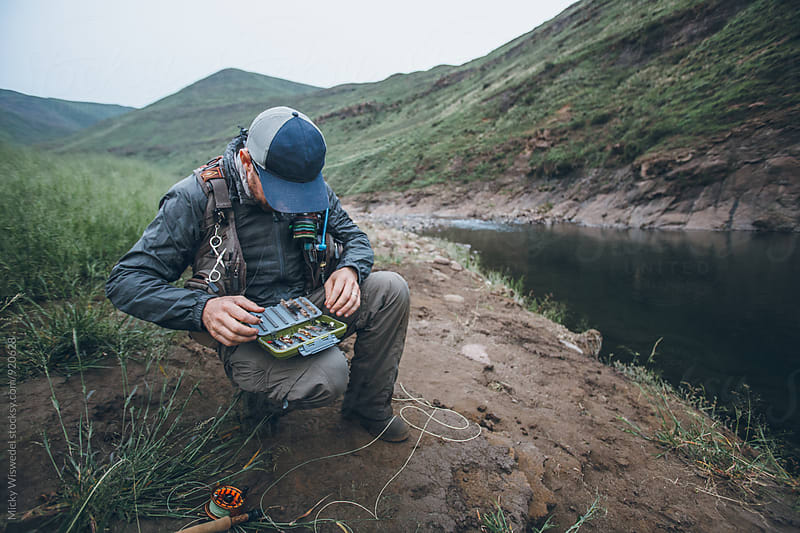 fly fisherman finding a new fly alongside a mountain river by Micky Wiswedel for Stocksy United