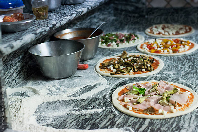 Pizzas made in a kitchen ready for cooking by Mike Marlowe for Stocksy United