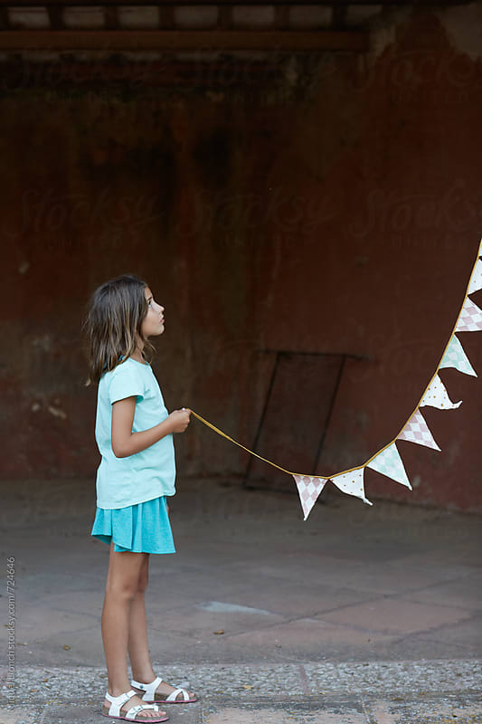 Young girl helping with the decoration of a party  by Miquel Llonch for Stocksy United