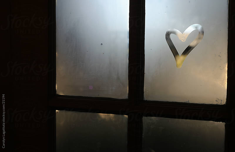 A small heart drawn on a fogged up window with light behind it. by Carolyn Lagattuta for Stocksy United