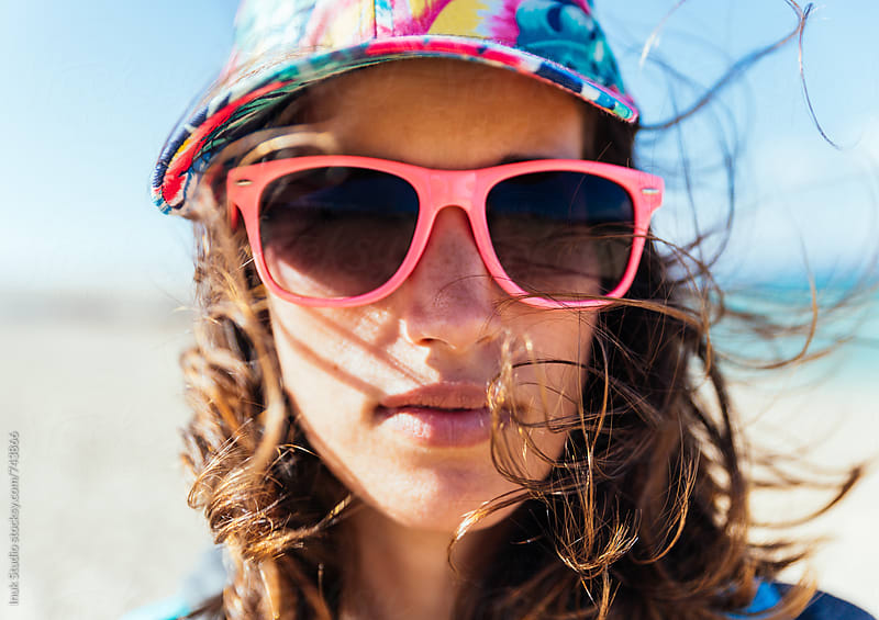 Stylish young woman portrait with sunglasses and colourful cap in a windy beach with her hair being blown by the wind by Inuk Studio for Stocksy United