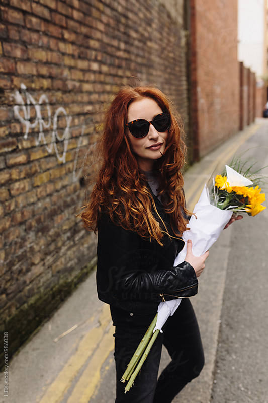 Beautiful Redhaed Girl Walking in the City with Sunflowers by HEX. for Stocksy United