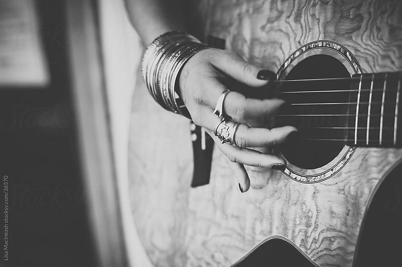 woman's hand with dark nail polish and numerous silver bangles playing guitar by Lisa MacIntosh for Stocksy United