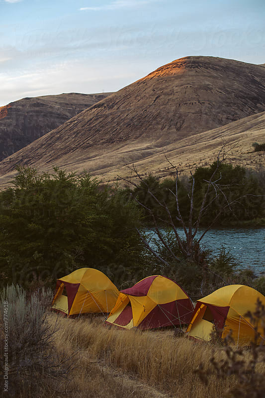 Desert canyon camp with a large river running through it.  by Kate Daigneault for Stocksy United