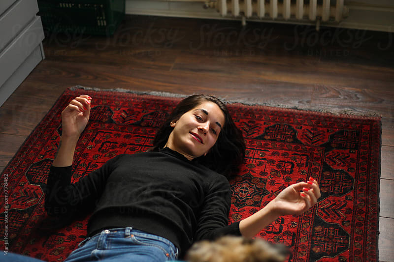 Woman smiling, lying on the floor by Marija Kovac for Stocksy United