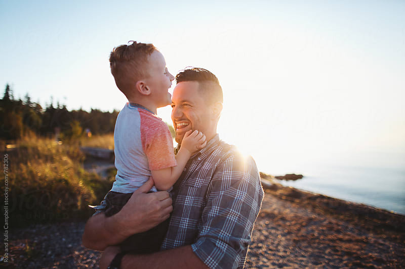 Energetic dad playing with son at sunset near water by Rob and Julia Campbell for Stocksy United