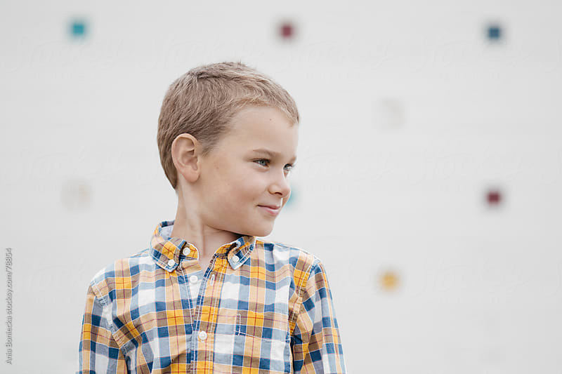 A blonde boy in a plaid shirt looking away by Ania Boniecka for Stocksy United
