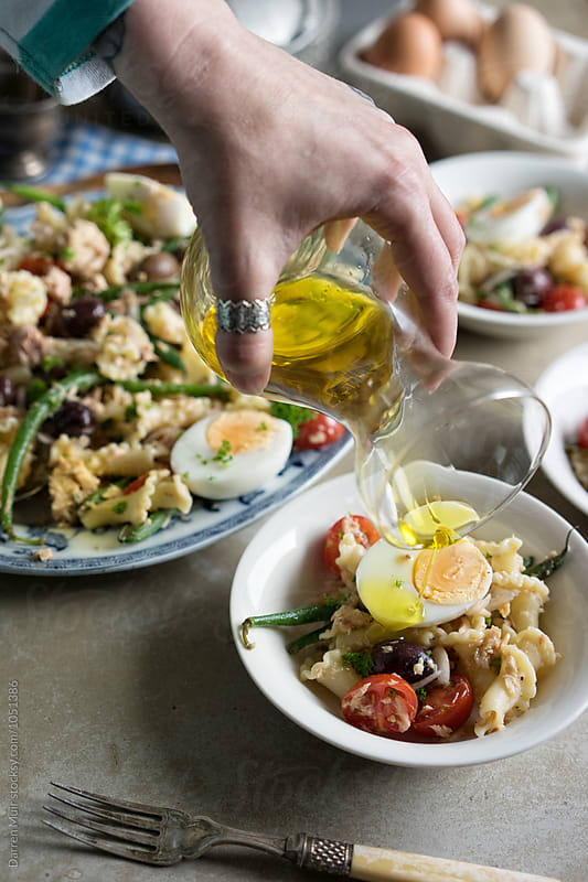 Tuna nicoise pasta salad. Hand pouring olive oil dressing over a salad. by Darren Muir for Stocksy United