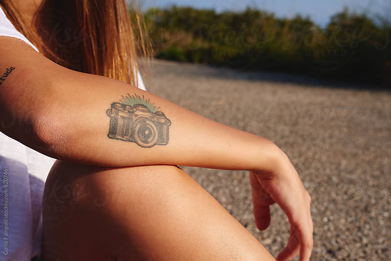 Young woman with camera tattoo on forearm by Guille Faingold for Stocksy United