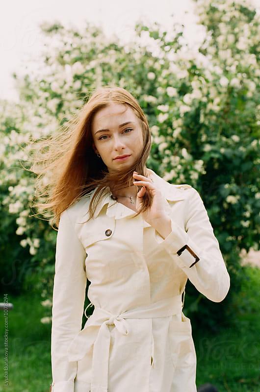 Portrait of young woman posing  outdoors by Liubov Burakova for Stocksy United