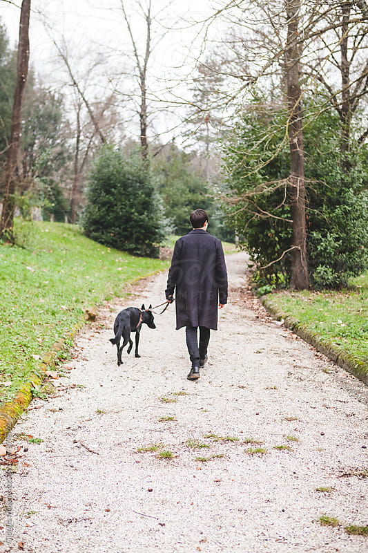Man with Black Coat Walking with His Dog at the Park during the Cold Season by Giorgio Magini for Stocksy United