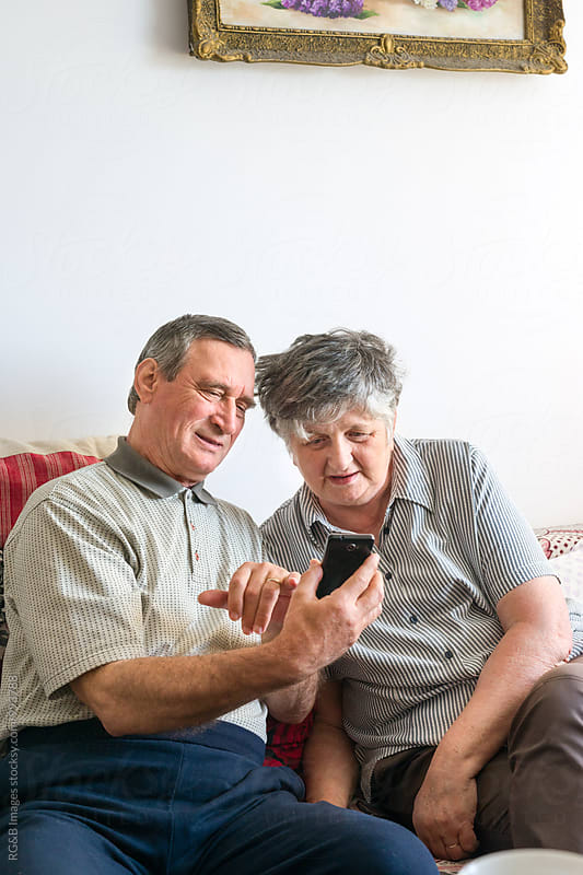 Elder couple using a smartphone together by RG&B Images for Stocksy United