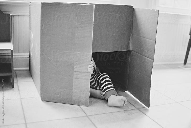 A foot of a young child sticking out of a box by Jakob for Stocksy United