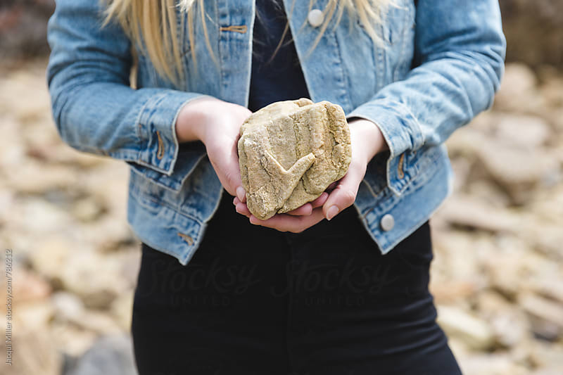 Girl holding a found rock with an unusual heart shape by Jacqui Miller for Stocksy United