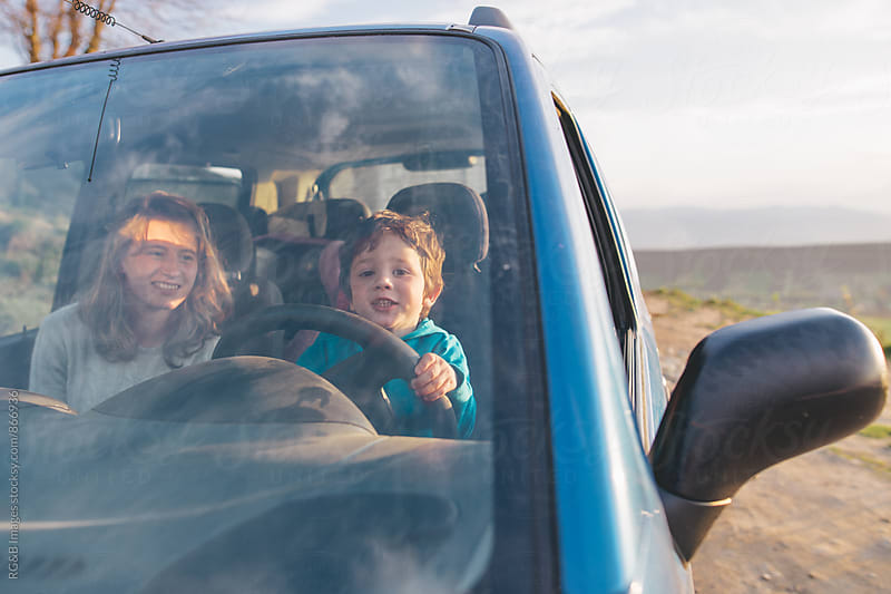 Kid driving parents' car by RG&B Images for Stocksy United