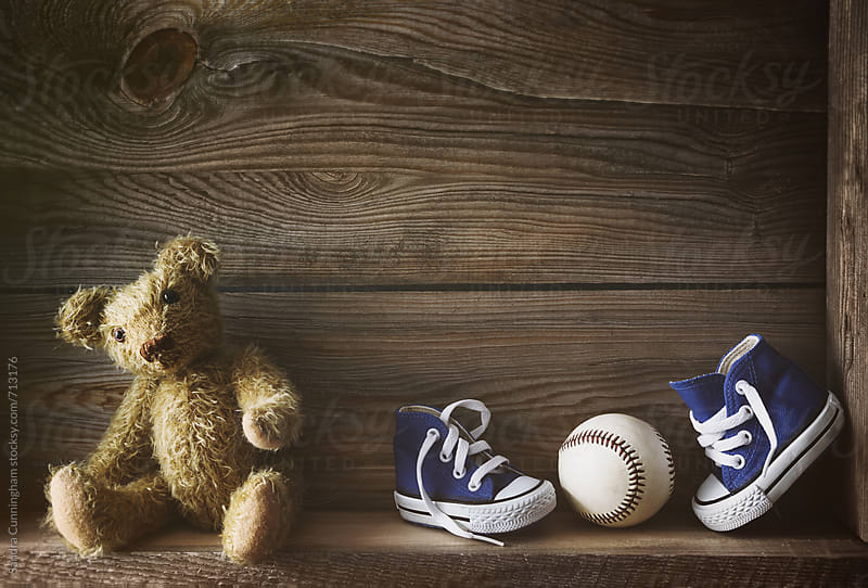 Little running shoes with teddy bear on shelf by Sandra Cunningham for Stocksy United