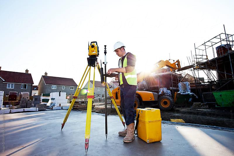 Surveyor using theodolite on building site.  by Hugh Sitton for Stocksy United