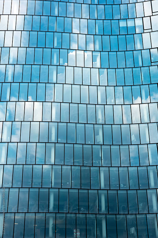 Blue sky and clouds reflected in offices windows by Luca Pierro for Stocksy United