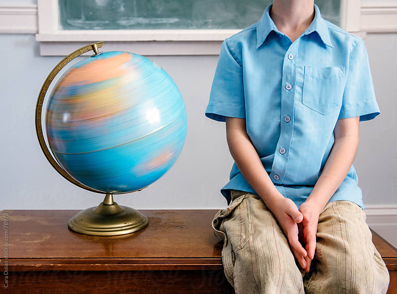 Child in classroom sits next to spinning globe by Cara Dolan for Stocksy United
