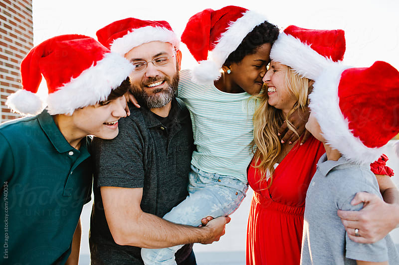 Happy Mixed-Race Family in Santa Claus Hats by Erin Drago for Stocksy United