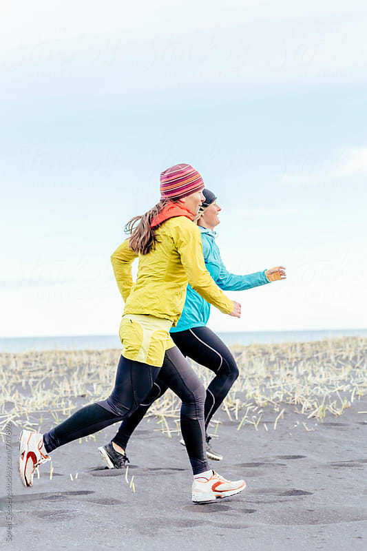 Two fitness girls running together on the beach by Soren Egeberg for Stocksy United